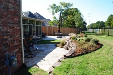 Flagstone patio with stacked rock wall retaining wall