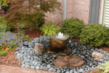 Half boulder fountain surrounded by Mexican beach pebbles